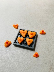 Eight cute heart shaped handmade clay plasticines. Four of these valentine's symbol are set on a piece of plastic construction toy. Four more are placed on grey tile surface. A warm message of love.