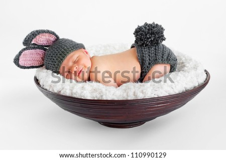 Eight day old smiling newborn baby boy wearing bunny ears and tail. He is sleeping on his stomach in a basket. Shot in the studio on an isolated white background.