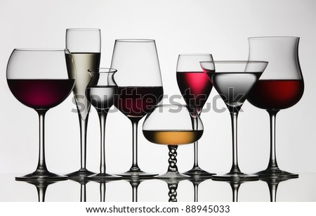 Eight difference glasses of wine and spirit, on a mirror and white background. #88945033