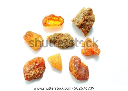 Eight different pieces of amber on a white background. Amber of various colors and structure and shapes. Transparent and opaque pieces of amber. Natural amber #582676939