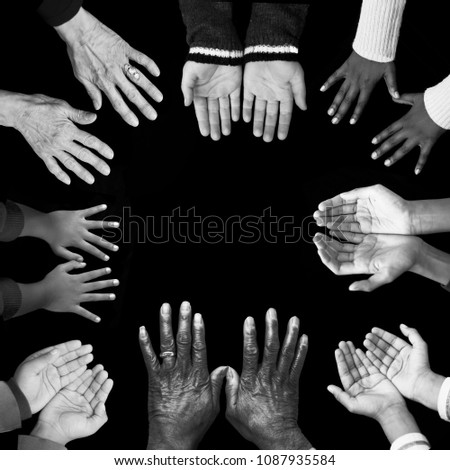 Eight diverse, unique sets of hands reach into the image, bordering a solid black square background. Young and old, diverse in color, size and age. Black, Caucasian, Indian and Asian skin colors. #1087935584
