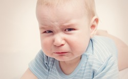 Eight month old baby crying. Sad child portrait