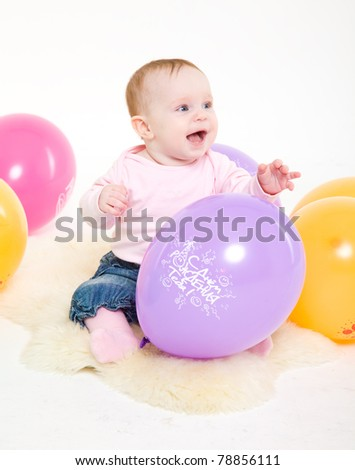 eight-monthly girl in a pink jacket and jeans with multi-colored balloons. A white background, it is isolated.