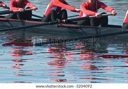 Eight oar sweep boat team readies for competition - reflection of rowers in rippled water