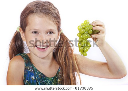 eight year old girl eating freshly picked grapes from the garden