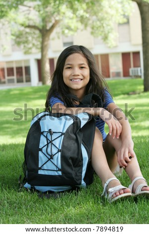 Eight year old girl with backpack in front of school.