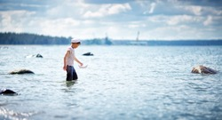 eight years old boy playing at the beach in sailor hat. Child walking in the water with paper ship at sea