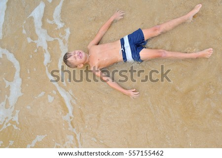 Eight years old handsome blond boy lying on the sand, eyes shut, attracted waves rolls and cover him as if coverlet, view from above #557155462