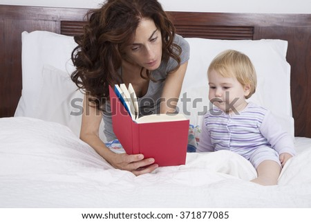 eighteen month aged blonde baby with brunette woman mother reading tale story red book in white bed