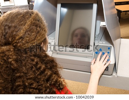 Eighteen year old girl voting for the first time on a touch screen machine.