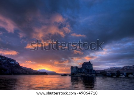 Eilean Donan Castle at sunset with reflections and views of the Cullins