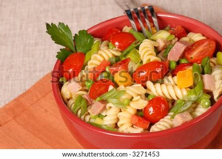 Ein frischer Teigwarensalat in einer roten Schüssel - stock photo