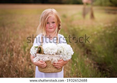 Ein Mädchen steht in einem gelben Feld, sie hat ein Körpchen mit den weißen Blumen.Sie sieht aus wie eine Bauernmädchen aus, hat süße Zöpfe, Die Haare sind durcheinander Сток-фото ©