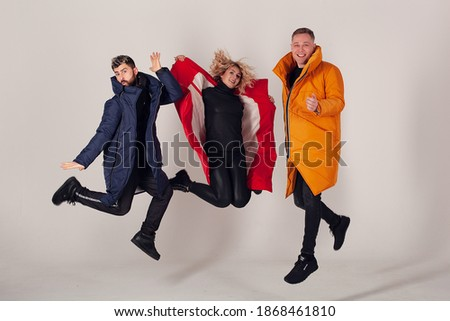 Photo of  Eject of blur from jump dynamics. Three models on a white background are dressed in winter clothes of different colors. The emotion of joy and delight. Three friends fooling around