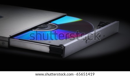 Ejecting or Inserting  cd, dvd or blue-ray disk into drive  without a computer on a black background