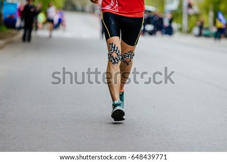 Ekaterinburg, Russia - May 21, 2017: feet men runner injury kinesiotape knee running on road in City half marathon #648439771