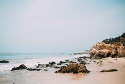 El Matador beach in California. Natural rocky beach in Malibu. Cliffs by the ocean. Rocky coast. Light blue water and white sand.