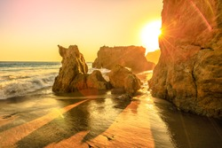 El Matador State Beach, California, United States. Sunbeams with sunset lights between pillars and rock formations of most photographed and scenic of Malibu beach, Pacific Ocean. California West Coast