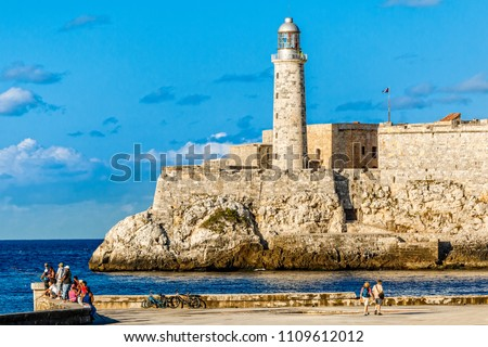 El Morro spanish fortress walls with lighthouse, walking people and fishermen in the foreground, Havana, Cuba