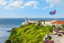 El Morro Spanish fortress with lighthouse, cannons and Cuban flag in th foreground, with sea in the background, Havana, Cuba
