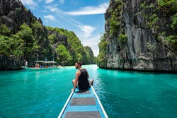 El Nido, Palawan, Philippines, traveler sitting on boat deck exploring the natural sights around El Nido on a sunny day.