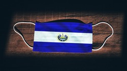 El Salvador National Flag at medical, surgical, protection mask on black wooden background. Coronavirus Covid–19, Prevent infection, illness or flu. State of Emergency, Lockdown