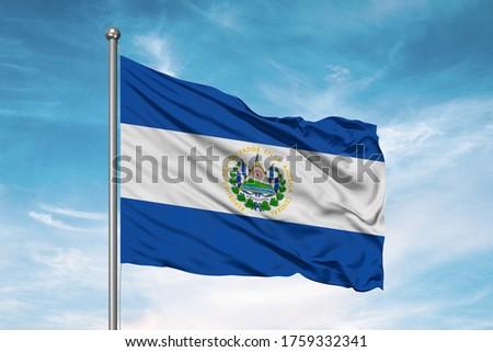 El Salvador national flag cloth fabric waving on beautiful sky.