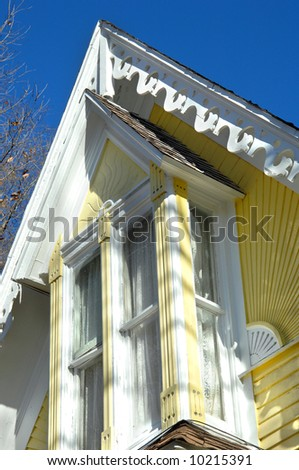 Elaborate eaves are trimmed in Victorian style.  Yellow and white painted.  Blue sky.