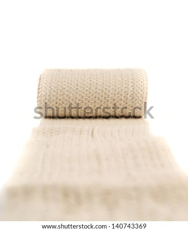 Elastic ACE compression bandage warp unwrapped over white background, shallow depth of field #140743369