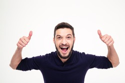 Elated excited young happy man with beard shouting and showing thumbs up with both hands over white background