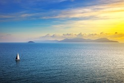 Elba island sunset view from Piombino an sail boat yacht. Mediterranean sea. Tuscany, Italy