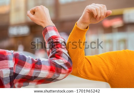 Elbow bump. Bump elbows. Friends shaking elbows outdoors. Elbow greeting style. Coronavirus epidemic. Coronavirus, illness, infection, quarantine, COVID-19. Don't shake hands. Stop handshakes.
