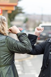 Elbow bump. New greeting to avoid the spread of coronavirus. Two women friends meet in British street with bare hands. Instead of greeting with a hug or handshake, they bump elbows instead. Vertical.