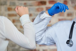 Elbow bumping. A new way of greeting to avoid the spread of coronavirus (COVID-19). A doctor and a female patient bump elbows Instead of greeting with a hug or handshake against a brick wall.