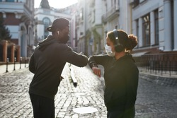 Elbow bumping. Young african couple of runners in medical protective masks bumping elbows instead of greeting, standing at the empty city street in the morning. Social distance. Coronavirus epidemic