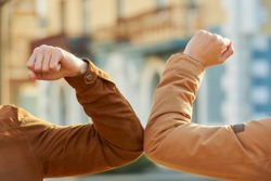 Elbow greeting to avoid the spread of coronavirus (COVID-19). A guy and a girl meet in the street with bare hands. Instead of greeting with a hug or handshake, they bump elbows instead.