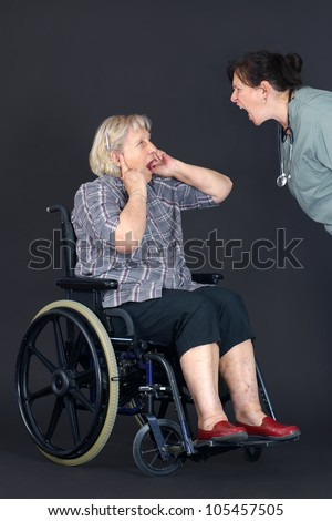Elder abuse concept with a senior woman in a wheelchair crying and covering her ears as a middle age nurse or other health care worker is yelling at her.