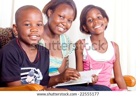 Elder african sister reads to her younger brother and sister