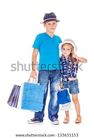 Elder boy and preschool girl in denim wear with customer paper bags
