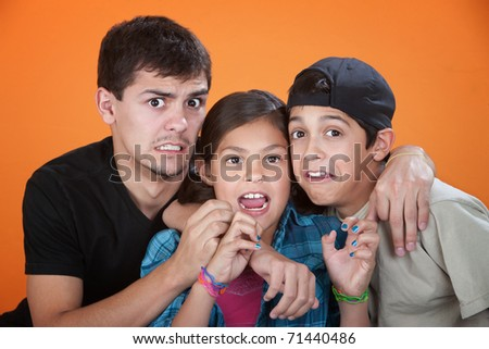 Elder brother with two younger siblings wearing a scared look