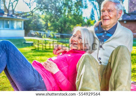 Elder couple smiling and relaxing seated in the garden. #554929564