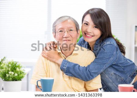 Elder father and young daughter smile to you happily