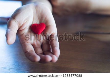 Elder Female hands giving little red heart , Love and care concept #1283577088