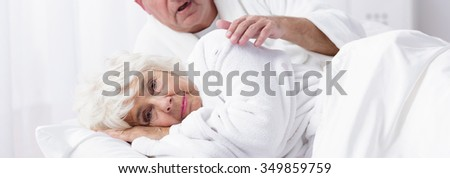 Elder lady is lying on the bed #349859759