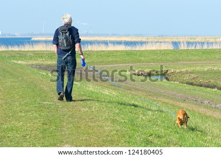Elder man is hiking with dog in nature near big lake