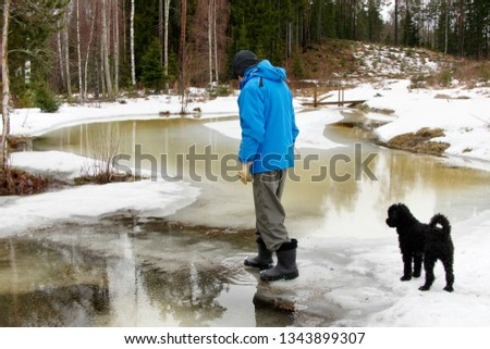 elder man with his dog walking over flooded river bank on a rainy day in wintry landscape #1343899307