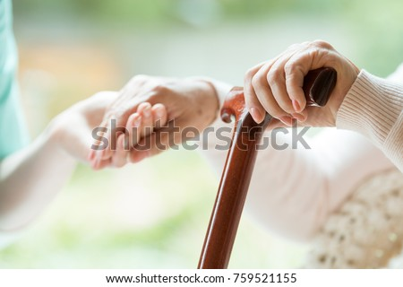 Elder person using wooden walking cane during rehabilitation in friendly hospital
