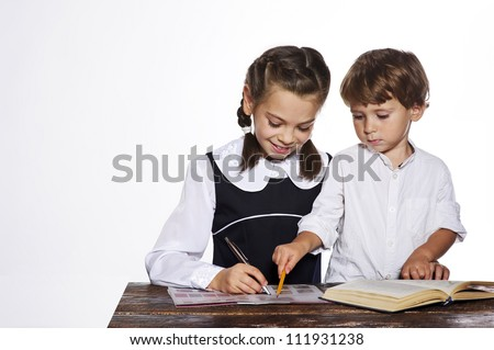 Elder sister trying to teach how to write her little brother.