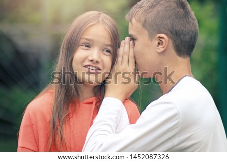 Elder teenager brother telling a secret in ear to his little shocked smiling cute teenage sister outdoors in the park