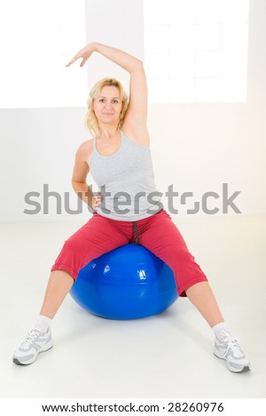Elder woman dressed sportswear exercising with fitness ball. She's looking at camera.